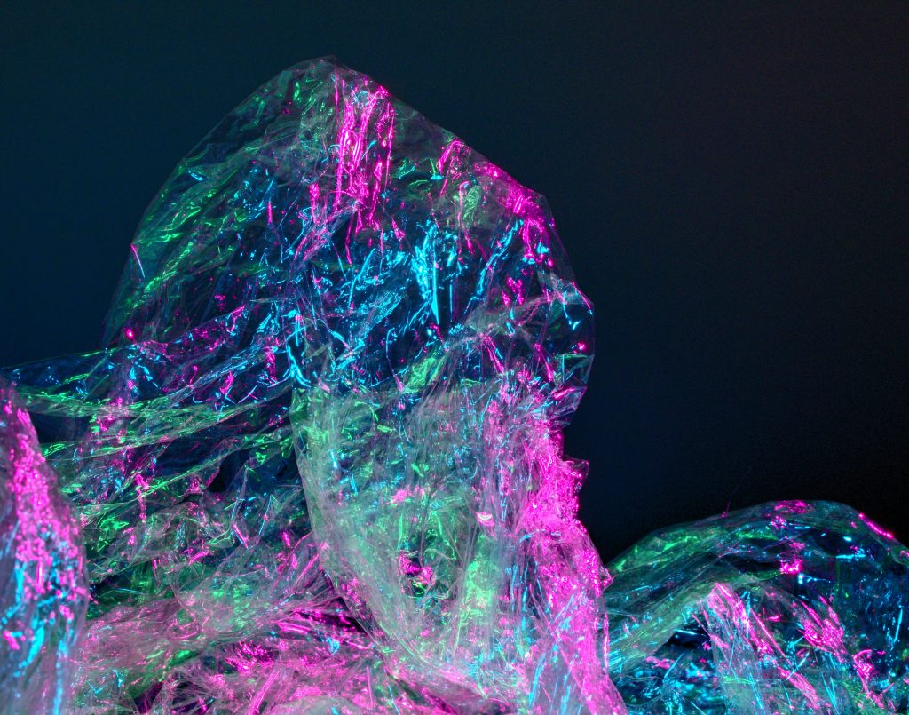 closeup of a plastic sheet with pink and blue lighting reflecting off of it