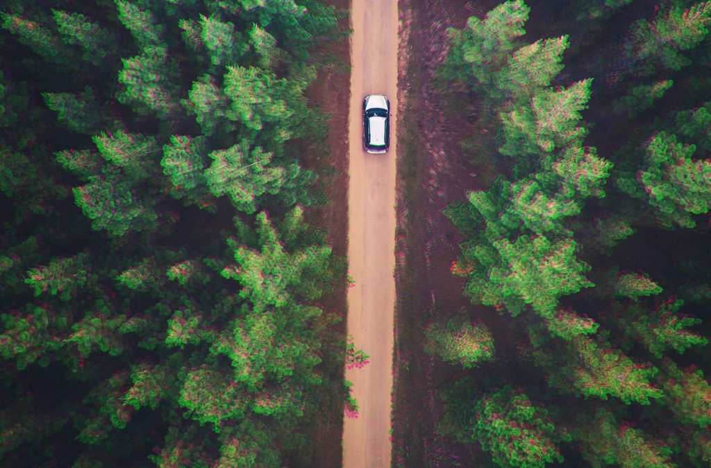 arial shot of a car going through a forest on a dirt track.