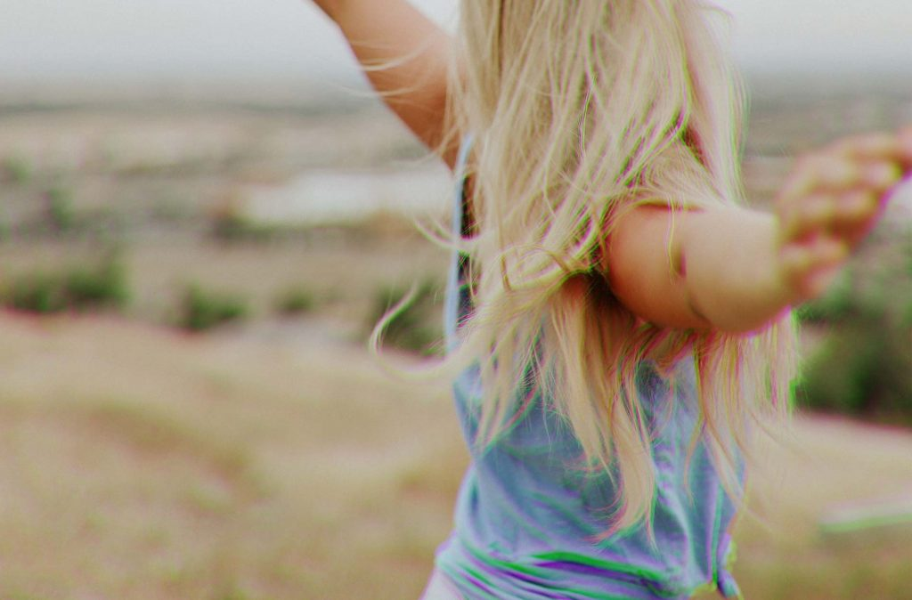Blonde girl spinning around with a blue top on, on top of a hill. Her arms are out and you can only see the back of her hair.
