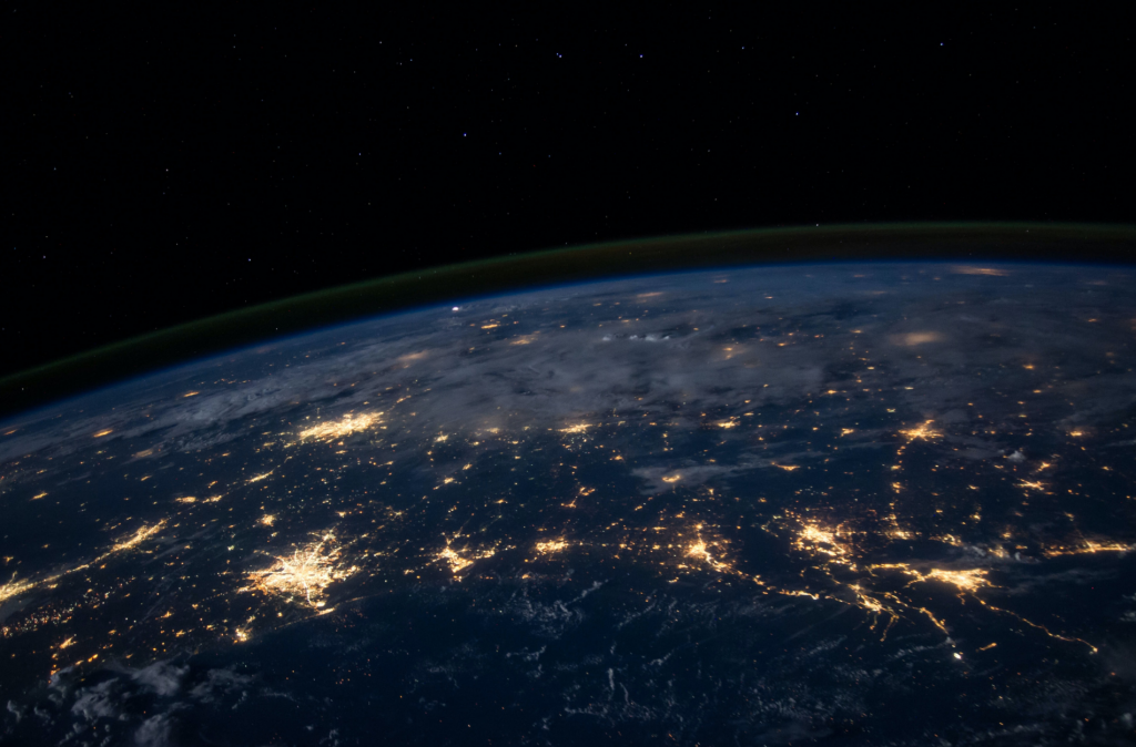 a satellite image of planet Earth at night, with electric lights showing in the cities