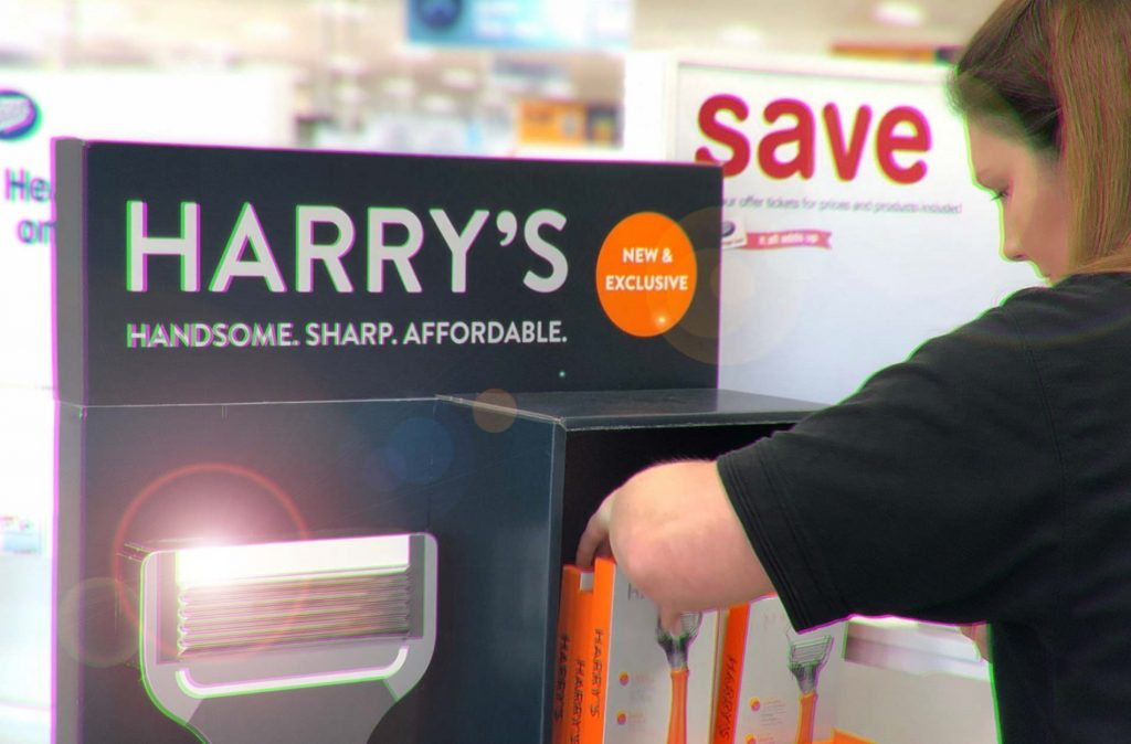 a woman moving boxes of razors around on a Harry's stand in a Boots store