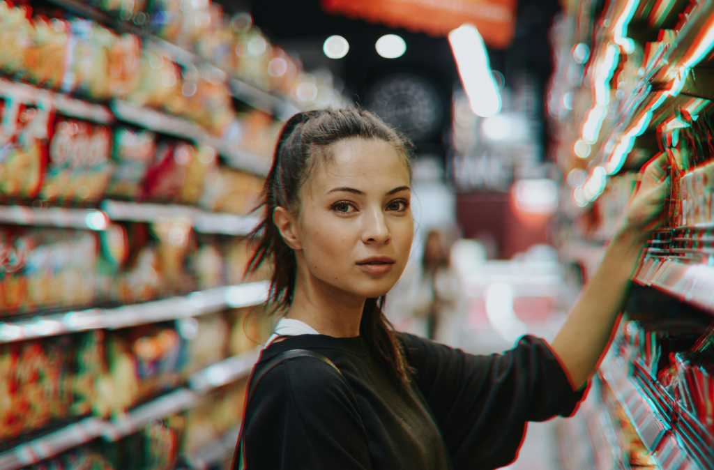 A woman facing the camera in a supermarket aisle. She is reaching for a product on the shelf.