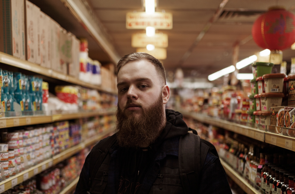 Man standing in supermarket aisle