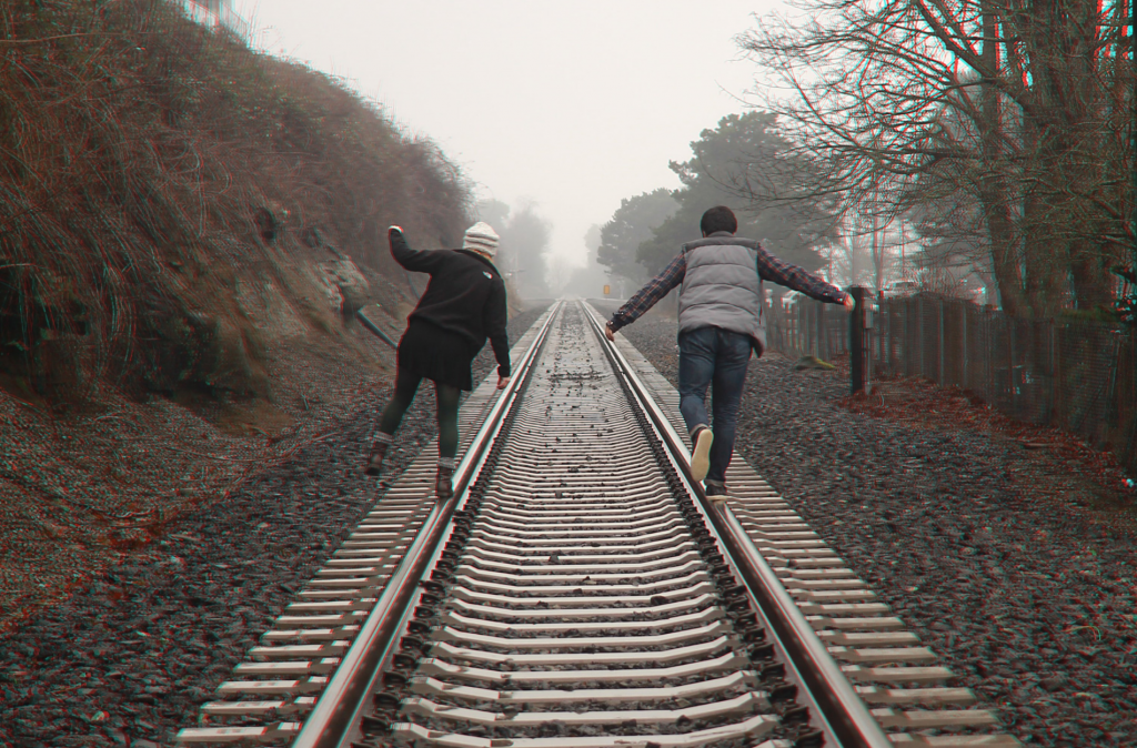 two people walking on a traintrack