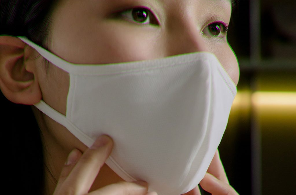 closeup of an asian woman wearing a white protective mask